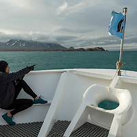 A woman points from the bow of the National Geographic Orion while exploring in Royal Bay on the north coast of South Georgia Island.