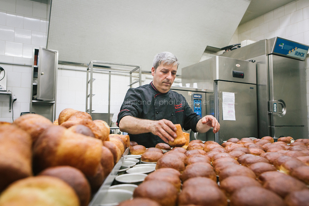 NAPLES, ITALY - 14 JULY 2017: Raffaele Capparelli (52), owner of the Pasticceria Capriccio, pulls out of the freshly baked babas out of their alluminium cups in his workshop in Naples, Italy, on July 14th 2017. Raffaele Capparelli is a patissier since 1984, when he inherited the art of pastry making from his father.<br /> <br /> The bab&agrave; is a small yeast cake saturated in syrup made with hard liquor, usually rum, and sometimes filled with whipped cream or pastry cream.<br /> <br /> The original form of the baba was similar to the babka, a tall, cylindrical yeast cake (babka is still cooked in Ukraine, Poland and in Ukrainian and Polish communities over the world). The name means &quot;old woman&quot; or &quot;grandmother&quot; in the Slavic languages; babka is a diminutive of baba.<br /> <br /> The modern baba au rhum (rum baba), with dried fruit and soaking in rum, was invented in the rue Montorgueil in Paris, France, in 1835 or before.<br /> <br /> The baba was later brought to Naples by Neapolitan cooks sent by Maria Carolina of Austria, the wife of the Spanish King Ferdinand I of Bourbon, to her sister Marie Antoinette.