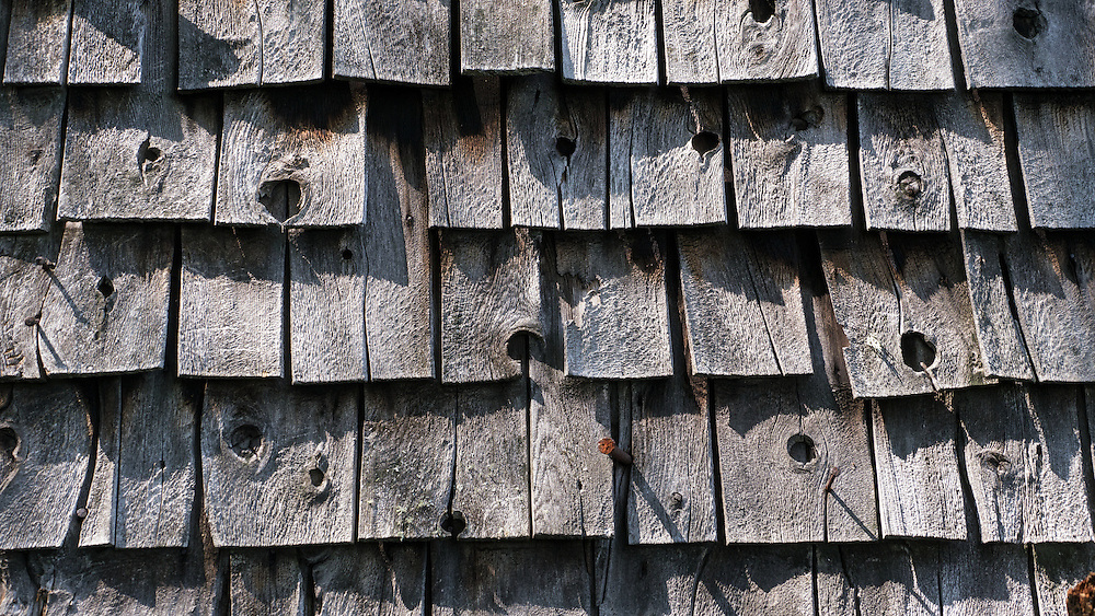 Old weathered warped wooden roof shingles sparkle in sunlight.