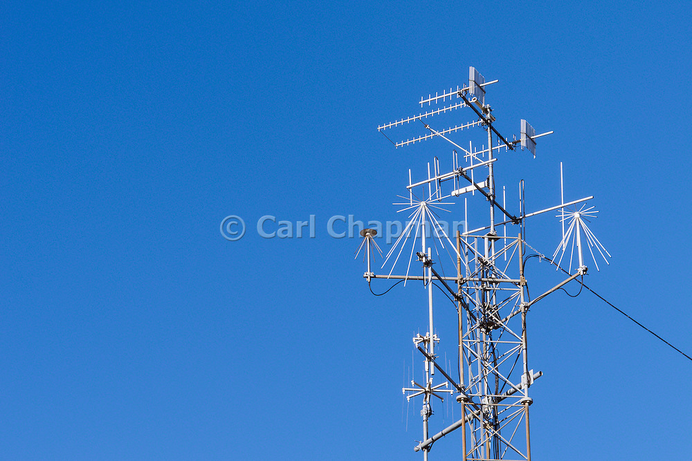 Yagi and discone communications antennas on triangular lattice tower for UHF and VHF wireless monitoring and surveillance station with direction finding.