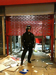 © licensed to London News Pictures. London, UK. 08/08/11. A police officer guards a shop during Rioting in croydon, London.  Photo credit should read Jules Mattsson/LNP
