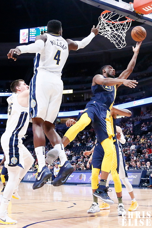 03 April 2018: Indiana Pacers forward Thaddeus Young (21) goes for the reverse layup past Denver Nuggets center Nikola Jokic (15) and Denver Nuggets forward Paul Millsap (4) during the Denver Nuggets 107-104 victory over the Indiana Pacers, at the Pepsi Center, Denver, Colorado, USA.