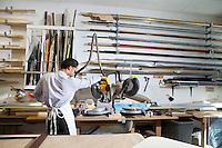 Back view of young man using circular saw in workshop