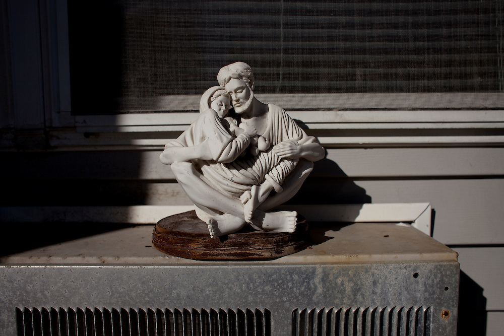 A pietà sculpture sits on the air conditioning unit outside of Meals on Wheels client Gerald Grubb in Cedar Rapids, Iowa on Thursday, November 19, 2015. (Rebecca F. Miller/Freelance for The Gazette)