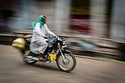 A panning shot of a milkman riding his motorbike through the main street of Old Bundi. Milkmen are ubiquitous in the Bundi mornings, selling milk door to door.