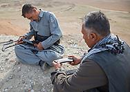 Iraq, Kurdistan, Kirkuk, kurdish peshmergas cleaning their kalashnikovs on the frontline