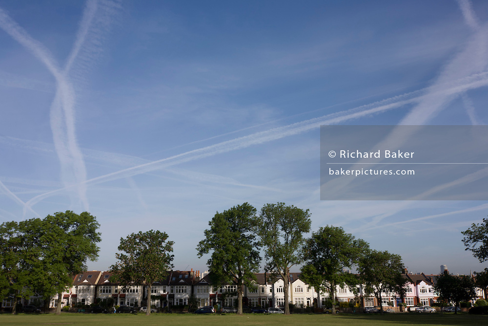 Vapour trails from overhead aviation leaves patterns above Period Edwardian London residential street in Ruskin Park, Lambeth.