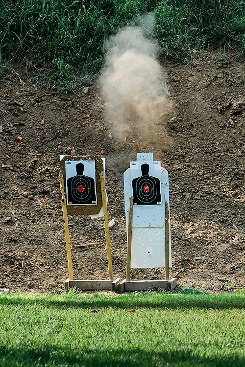 A puff of dirt rises from behind the shooting target 50 yards away.