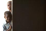 Boys peeking into a doorway.