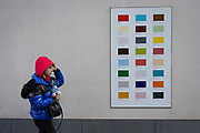 A woman wearing bright blue and red walks past a colour swatch on the wall of a central London business, on 22nd November 2017, in London England.