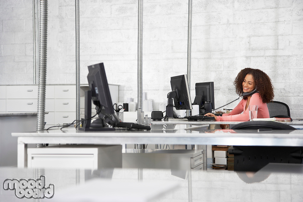 Young woman in office using computer and phone smiling