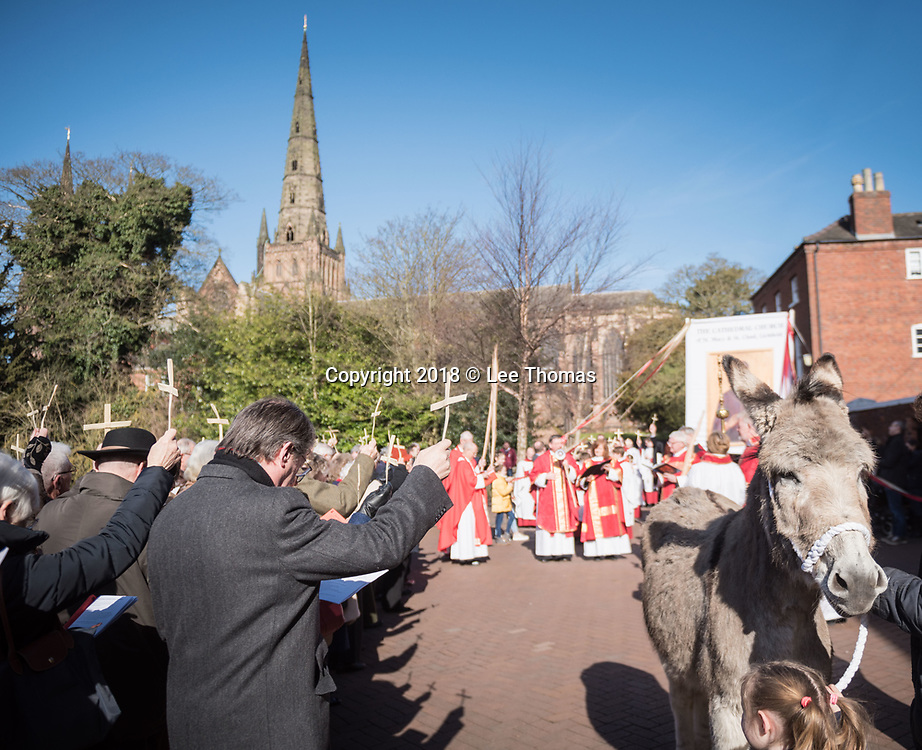 "Lichfield, Staffordshire, UK. 25th March 2018.  A fine spring morning greeted worshipers, members of the clergy and a donkey for the annual Palm Sunday procession through the medieval streets of Lichfield. The ""Triumphal Entry"" procession (when Jesus entered Jerusalem cheered on by a crowd, riding on a donkey) began at Speakers' Corner in the Staffordshire city and ended at the west door of the famous Cathedral. Pictured: Worshippers hold up their Palm crosses at Speakers' Corner at the beginning of the ceremony. // Lee Thomas, Tel. 07784142973. Email: leepthomas@gmail.com  www.leept.co.uk (0000635435)"