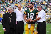 Bishop David Ricken, left, Denis Hogan and Jerry Pigeon present Green Bay Packers quarterback Aaron Rodgers with the Most Valuable Player award for his performance in the 2009 Charities game prior to last year's Bishop's Charities Game at Lambeau Field. On Sept. 1, Rodgers and tight end Jermichael Finley will be presented co-MVP trophies for last year's BIshop's Charities Game. (Renae Bauer | For The Compass)