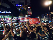 After several hours on Mehmet's street, the young men pile into cars around midnight (on a Tuesday) and drive toward Istanbul's old city, chanting slogans and leaning on their horns. They occasionally get out of their vehicles and block traffic as they revel in the middle of the road, tossing Mehmet in the air.