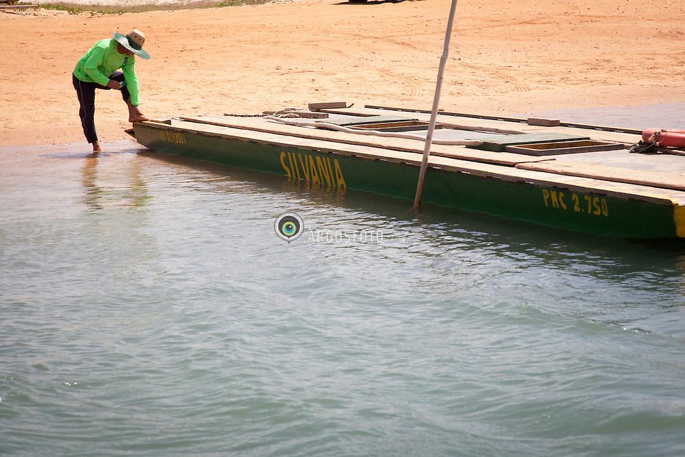 Homem retirando a balsa da agua em  Barra do Rio Ceara Mirim, Genipabu para Pitangui./ Man pulling  the ferry from water in Barra do Rio Ceara Mirim, Genipabu to Pitangui. Rio Grande do Norte, Brasil - 2013