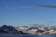 Gibbous moon hangs over glaciers and mountains of Smeerenburgfjorden along coast of Spitsbergen island; Svalbard, Norway.