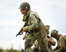 "Re-enactors from the Northern World War Two Association Living History group portraying the American 101st Airborne ""Screaming Eagles"" advancing during a large scale battle re-enactment. SPAM 1940's Weekend. Heckmonwyke near Wakefield 10 July 2010 .Images © Paul David Drabble"