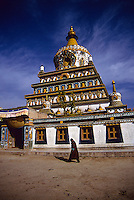 A tibetan nomad completes the kora around this temple near Rebkong in Qinghai province, China.