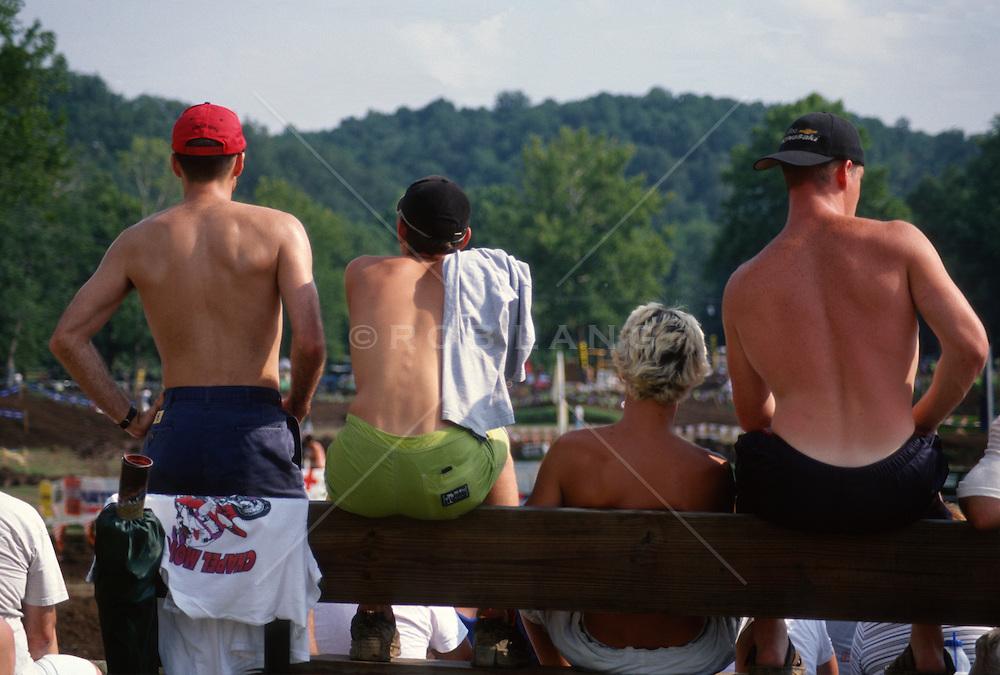 Shirtless backs of four guys watching a race
