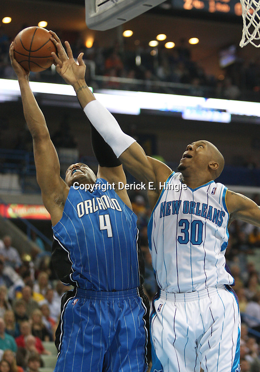 18 February 2009: Orlando Magic center Tony Battie (4) grabs a rebound over New Orleans Hornets forward David West (30) during a NBA basketball game between the Orlando Magic and the New Orleans Hornets at the New Orleans Arena in New Orleans, Louisiana.