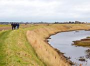 View from behind of people walking on path near Shingle Street, North Sea coast, Suffolk, England, UK