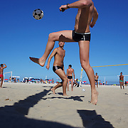 Locals practice foot  volley, a hybrid game combining beach volley ball and football at Copacabana beach, Rio de Janeiro,  Brazil. 4th July 2010. Photo Tim Clayton..The beaches of Rio de Janeiro, provide the ultimate playground for locals and tourists alike. Beach activity is in abundance as beach volley ball, football and a hybrid of the two, foot volley, are played day and night along the length and breadth of Rio's beaches. .Volleyball nets and football posts stretch along the cities coastline and are a hive of activity particularly at it's most famous beaches Copacabana and Ipanema. .The warm waters of the Atlantic Ocean provide the ideal conditions for a variety of water sports. Walkways along the edge of the beaches along with exercise stations and cycleways encourage sporting activity, even an outdoor gym is available at the Parque Do Arpoador overlooking the ocean. .On Sunday's the main roads along the beaches of Copacabana, Leblon and Ipanema are closed to traffic bringing out thousands of people of all ages to walk, run, jog, ride, skateboard and cycle more than 10 km of beachside roadway. .This sports mad city is about to become a worldwide sporting focus as they play host to the world's biggest sporting events with Brazil hosting the next Fifa World Cup in 2014 and Rio de Janeiro hosting the Olympic Games in 2016...