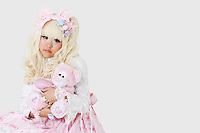 Portrait of cute woman dressed as a doll holding soft toy over gray background