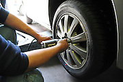 Mechanic uses pneumatic tool to secure the wheel on to the vehicle