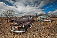 Car Graveyard of 1940s cars with dramatic clouds in early spring, shot at angle