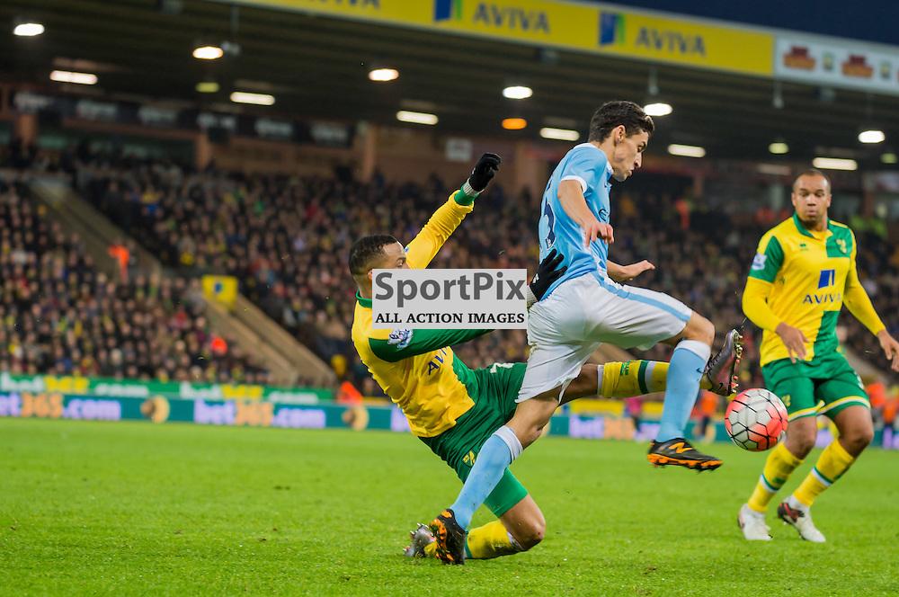 Manchester City midfielder Jesus Navas (15) holds off the challenge of Norwich City defender Sebastien Bassong (6)