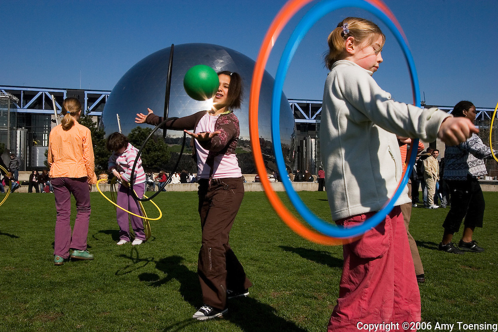 PARIS, FRANCE - APRIL 06: Girls play with hoola hoops on the lawns of Parc De La Villette April 6, 2006 in Paris, France. Half the world's population now lives in cities, and this proportion is expected to grow by sixty percent in the next twenty-five years. Urban parks are valued as public spaces that enhance almost everything about the cities they serve, from job opportunities, youth development, public health, community building and an appreciation for nature and conservation. Since most urban dwellers experience nature through city park systems, these slices of green take on more and more value. The city of Paris has over four hundred parks, ranging from the 2,000 acre Bois de Boulogne, to the Jardin d'Acclimatation for children, to the Promenade Plantee, the only elevated park in the world. (Photo by Amy Toensing) _________________________________<br /> <br /> For stock or print inquires, please email us at studio@moyer-toensing.com.