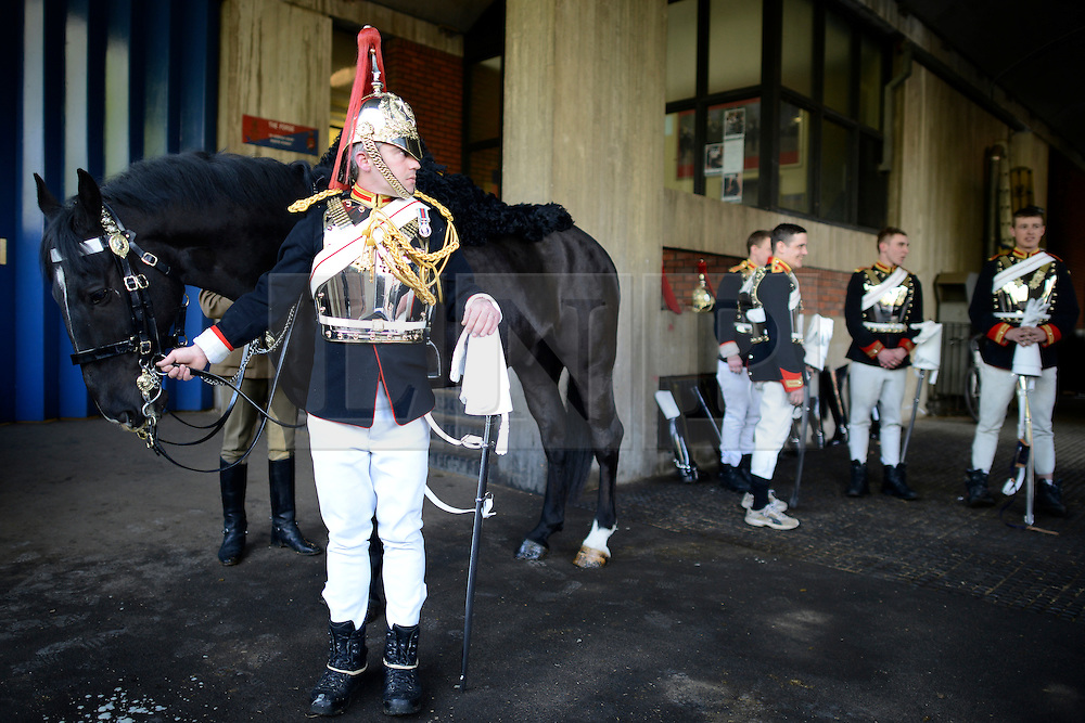 © Licensed to London News Pictures. 20/04/2012. London, UK . Soldiers wait for their horses to be brought from the stables. A Preview of the Household Cavalrys 'The Best of British' art exhibition. Soldiers walk around the artwork as they prepare to mount duties at Horse Guards Parade. The Queen's Life Guard are inspected before they depart the Barracks for the daily Guard change at 1100. The exhibition runs between 23 - 26 April. Hyde Park Barracks, Ceremonial Gate, South Carriage Drive, London, SW7 1SE. Photo credit : Stephen Simpson/LNP