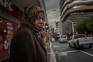 Weary woman prepares to cross a busy street in Cape Town's CBG district on a chilly winter day, as she heads home after the work day.  South Africa.