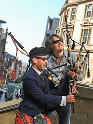 Pictured: Alasdair MacLaren (front) from Glasgow Police Pipe Band joins festival headliner Ross Ainslie in the sun at the launch.<br /> <br /> <br /> Glasgow Police Pipe Band were on hand to make sure the launch for this years Piping Live! Glasgow Piping Festival was no quiet affair outside Glasgow Royal Concert Hall.<br /> <br /> © Dave Johnston / EEm