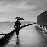 Two people along a stormy seawall, one running, one walking with an umbrella. Curved fence on one side and ocean on the other.