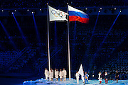 07.02.2014. Sochi, Krasnodar Krai, Russia.   The Olympic flag is seen flying beside that of host nation Russia during the Opening Ceremony of the XXII Olympic Winter Games at the Fisht Olympic Stadium