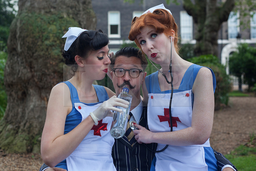 © licensed to London News Pictures. London, UK 08/07/2012. Two vintage nurse lookalikes posing with a man at the Chap Olympiad in Bedford Square Gardens in central London today. the Chap Olympiad describes itself as a celebration of eccentricity and athletic ineptitude with the emphasis on panache and style over sporting prowess. Photo credit: Tolga Akmen/LNP