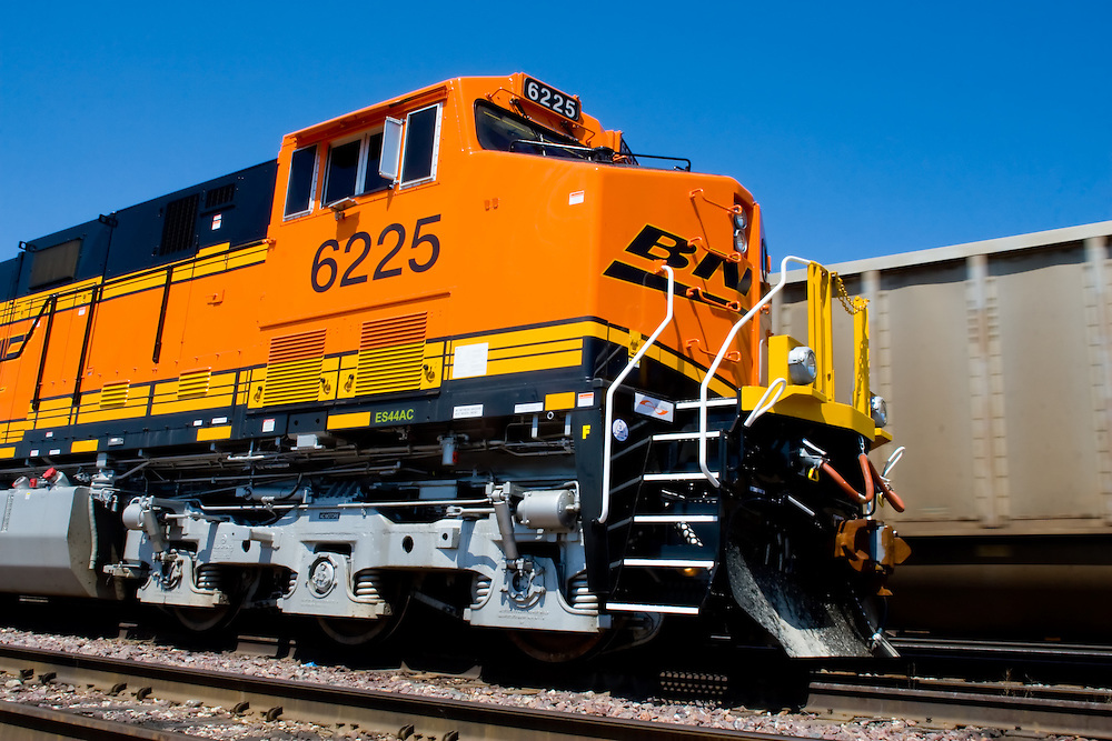 A brand new BNSF General Electric locomotive is parked as a loaded coal train moves out of the yards in Chicago, IL.