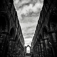 Remains of an Abbey, Imposing stone columns, old stone with imposing dark skies.