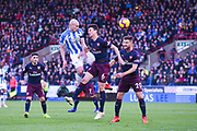 Aaron Mooy of Huddersfield Town (10) heads above Laurent Koscielny of Arsenal (6) and Shkodran Mustafi of Arsenal (20) during the Premier League match between Huddersfield Town and Arsenal at the John Smiths Stadium, Huddersfield, England on 9 February 2019.