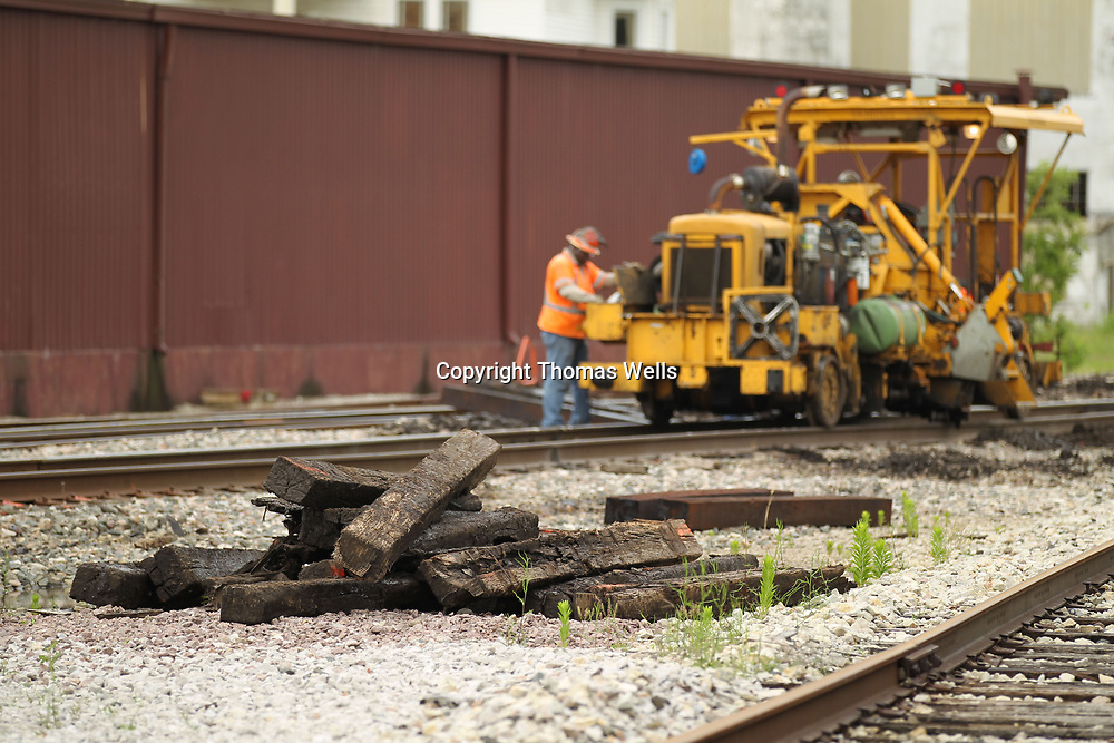 A stack of old cross-ties begin to build up as workers from Burlington Northern Santa Fe begin replacing old ties with new ones along the tracks through Tupelo on Monday.