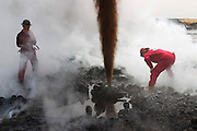 "Boots and Coots team members study a gushing oil well minutes after the fire was extinguished. The ground is still smoking. Well capped two hours later using a ""stinger,"" a tapered pipe on the end of a long steel boom controlled by a bulldozer. Drilling mud, under high pressure, is pumped through the stinger into the well, stopping the flow of oil and gas. The Rumaila field is one of Iraq's biggest oil fields with five billion barrels in reserve. Rumaila is also spelled Rumeilah."