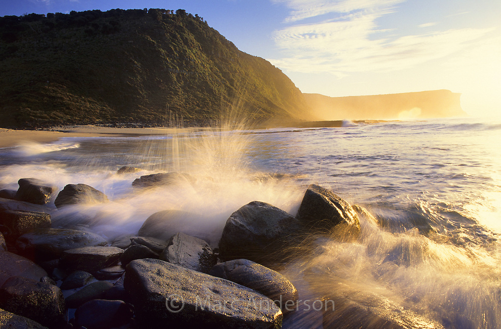 Waves crashing over rocks on a beach at dawn. Little Garie Beach, Royal National Park, Australia.