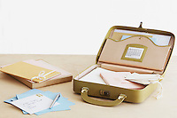 Postcard and envelopes next to suitcase with stationery items elevated view studio shot