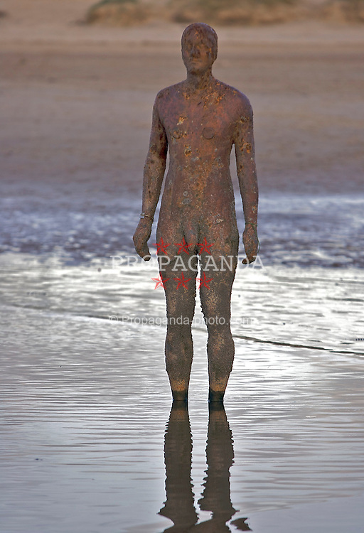 """SEFTON, ENGLAND - SUNDAY, OCTOBER 29th, 2006: One of the 100 Iron-men sculptures that comprise Anthony Gormley's Another Place art installation at Crosby Beach, Sefton. (Pic by David Rawcliffe/Propaganda)..Another place is a spectacular sculpture by Angel of the North artist Antony Gormley. Another Place consists of 100 cast-iron, life-size figures spread out along three kilometres of the foreshore, stretching almost one kilometre out to sea. Each one weighing 650 kilos and is made from casts of the artist's own body. They are shown at different stages of rising out of the sand, all of them looking out to sea, staring at the horizon in silent expectation. According to Antony Gormley, Another Place harnesses the ebb and flow of the tide to explore man's relationship with nature. He explains: """"The seaside is a good place to do this. Here time is tested by tide, architecture by the elements and the prevalence of sky seems to question the earth?s substance. In this work human life is tested against planetary time. This sculpture exposes to light and time the nakedness of a particular and peculiar body. It is no hero, no ideal, just the industrially reproduced body of a middle-aged man trying to remain standing and trying to breathe, facing a horizon busy with ships moving materials and manufactured things around the planet."""""""