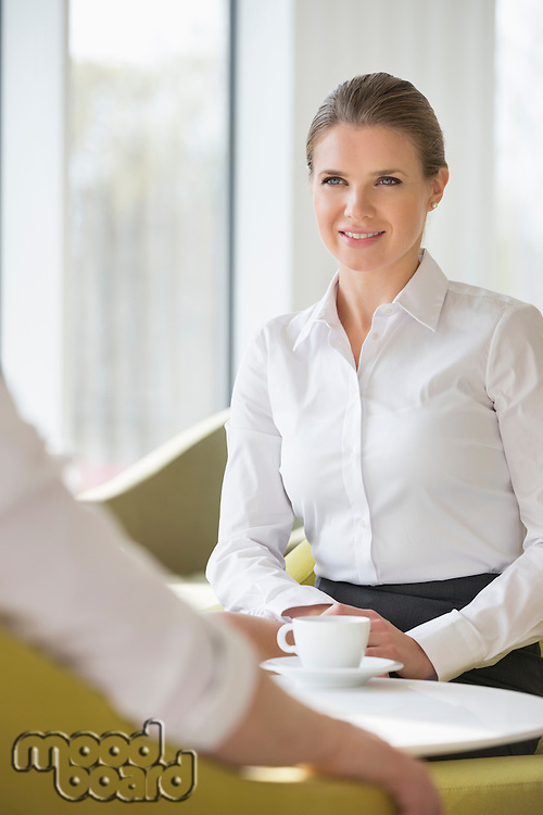 Smiling businesswoman with colleague at office lobby