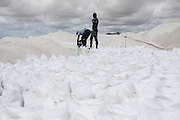 Workers labour closing the 25 kg bags of salt at the Lac Rose near Dakar, Senegal, on Tuesday, July 26, 2016. *** Second Sentence *** Photographer: Xaume Olleros/Bloomberg