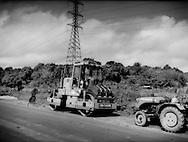 Most of the heavy machinery used by a paving crew from the Peoples Republic of China (PRC) are brought over from China, and the vast majority of workers are brought over from the PRC, as well.  Along the road into the interior between Paramaribo and Brokopondo, Suriname.   Those jobs filled by locals were largely for unskilled labor.