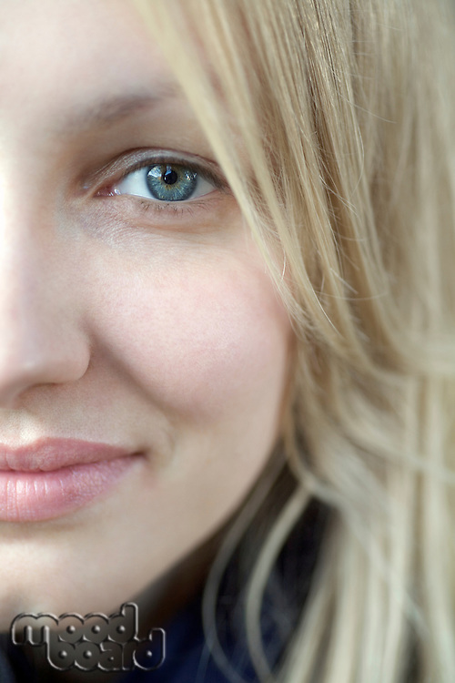 Half face of smiling blonde woman with blue eyes