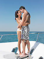 Young couple embracing on yacht looking in eyes and smiling